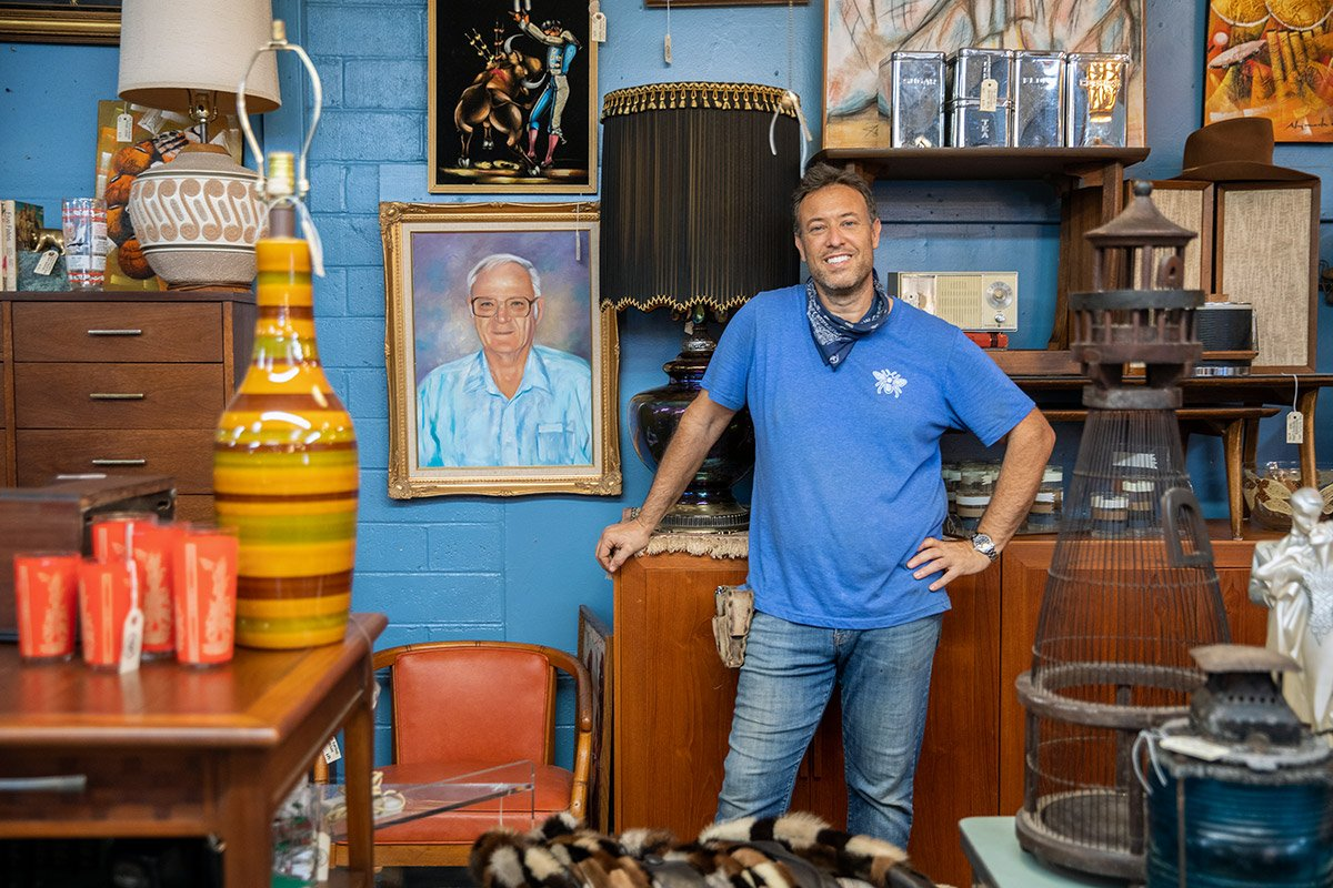 An owner of a vintage market stands next to vintage furniture and wall hangings at his store. He's wearing a blue shirt with a bandana around it.