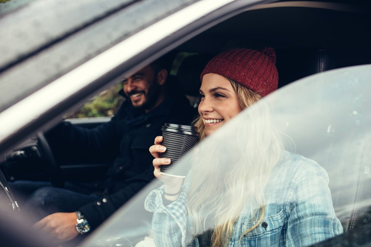 A young woman sips on coffee as she is about to leave on a road trip.